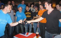 Competitors at the 4th UK Rock Paper Scissors Championships in 2010.  The game 'rock paper scissors' uses six words; three objects (nouns) and three actions (verbs), and is played without speaking.  Each player presents the other with an 'object', represented as a gesture.  The way these objects interact is already understood by the participants.  As they play, the phrases, i.e. the 'unspoken rules' of the game, come to mind (Image: Wikimedia Commons)