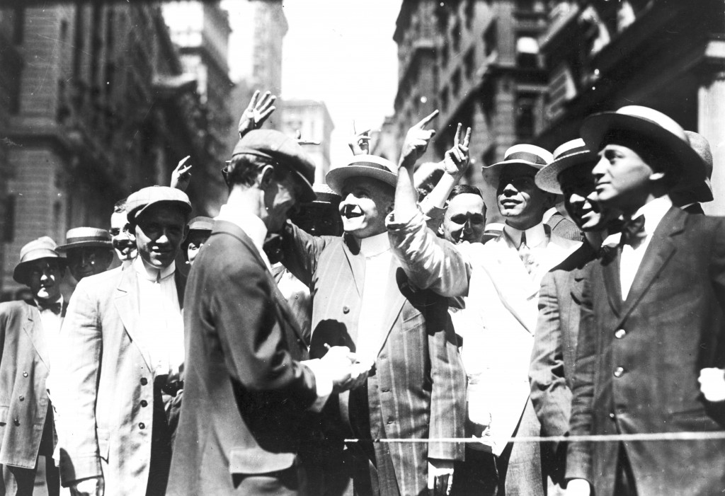 This photograph of the New York Curb Association market (c1916) shows brokers and clients signalling from street to offices using stylised gestures.  Similar manual signs have arisen in many open floor stock exchanges around the world, where they made it possible to broker rapid 'face-to-face' deals across a noisy room (known as the 'open outcry' method of trading).  Today these manual languages have been largely superseded by the advent of telephones and electronic trading through the 1980's and 1990's (Image: Wikimedia Commons)
