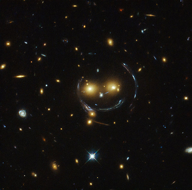 The arcs of the 'face' and 'smile' in this image of galaxy cluster SDSS J1038+4849 are caused by gravitational lensing. Gravitational lensing is where light is bent by a gravitational field (like around a galaxy) (Image: NASA/ESA, via Wikimedia Commons)